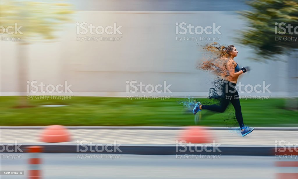 Particle decay effect. Sporty woman runing on street in sportswear. Training sun day. Big gray wall behind stock photo