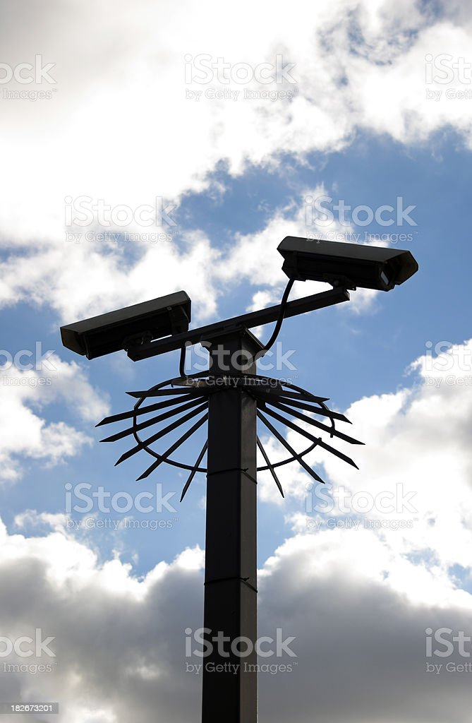 partly silhouetted security cameras stock photo