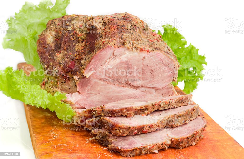 Partly sliced baked pork neck on cutting board closeup foto stock royalty-free