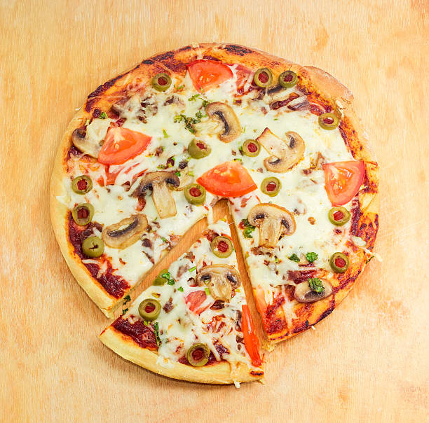 partly sliced cooked pizza with chicken, mushrooms, tomatoes and - gebackene champignons stock-fotos und bilder