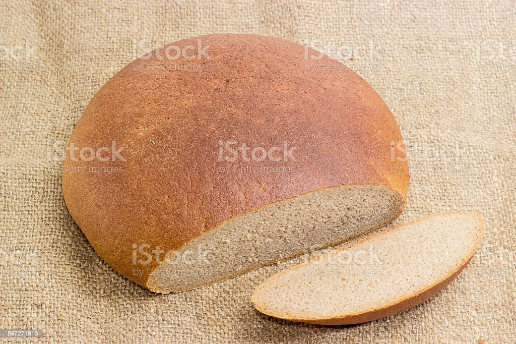 Partly sliced wheat rye hearth bread on a sackcloth royalty-free stock photo