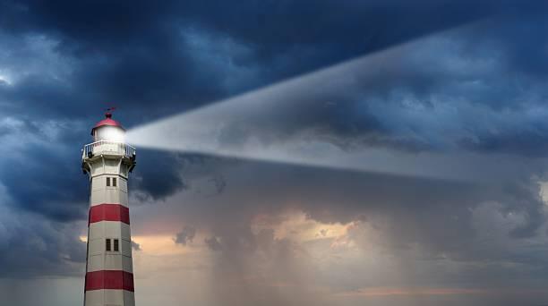 partiellement ensoleillé phare, mauvais temps en arrière-plan - phare photos et images de collection