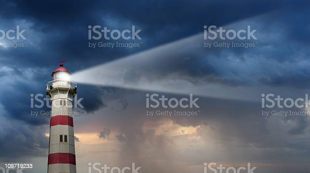Photo of Partly sunlit lighthouse, bad weather in background