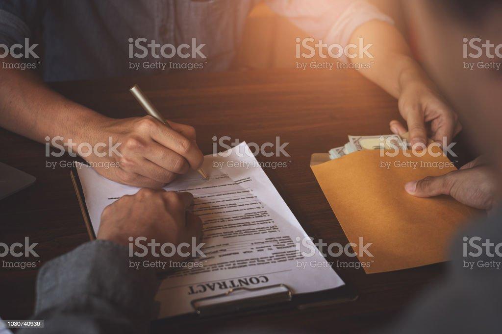 Partner geben Bestechungsgelder in Umschlag an einen anderen Unternehmer und zeigte auf Zeichen erlauben Vertrag. Korruption und Bestechung Anti-Konzepte. – Foto