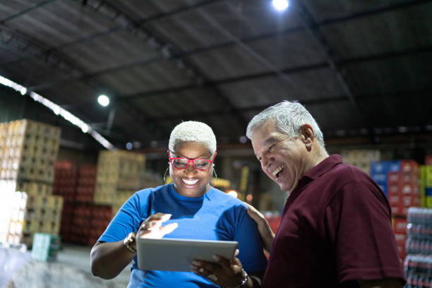partners celebrating good news and using digital tablet at warehouse - prodotti supermercato foto e immagini stock