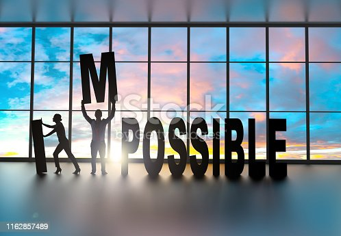 Silhouettes of business partners moving letter inside an office at sunset. They are removing the letters I and M from the word impossible to leave the word possible instead