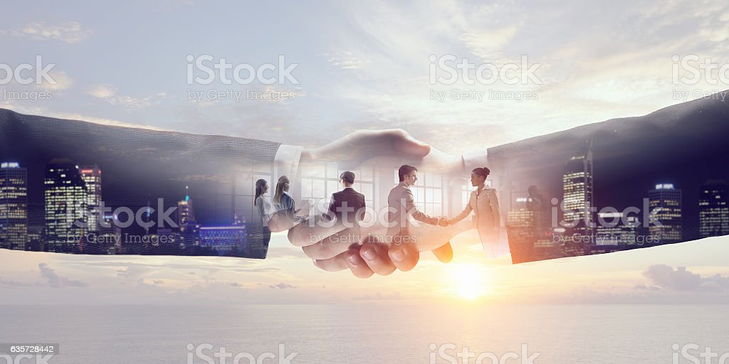 Partners shaking hands . Mixed media stock photo
