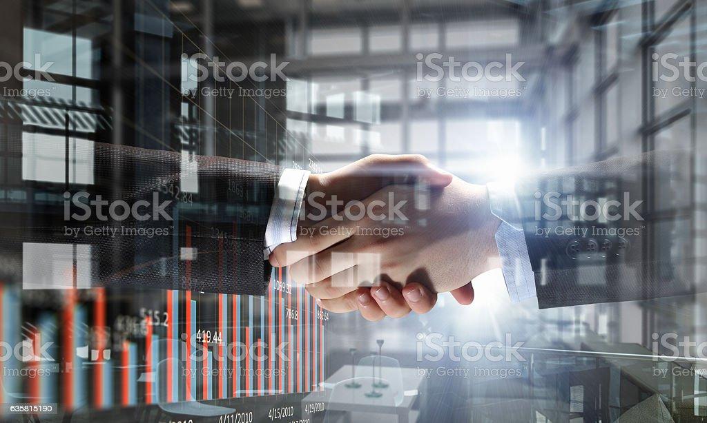 Partners shaking hands . Mixed media stock photo