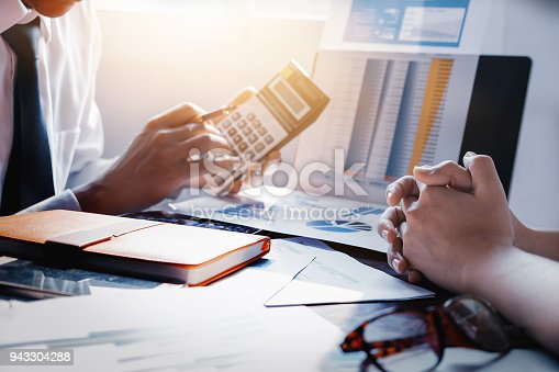942382022istockphoto partnership and Businessman using calculator are meeting to plan sales to meet targets set in next year. 943304288