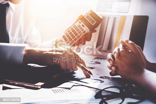 942382022istockphoto partnership and Businessman using calculator are meeting to plan sales to meet targets set in next year. 950229008