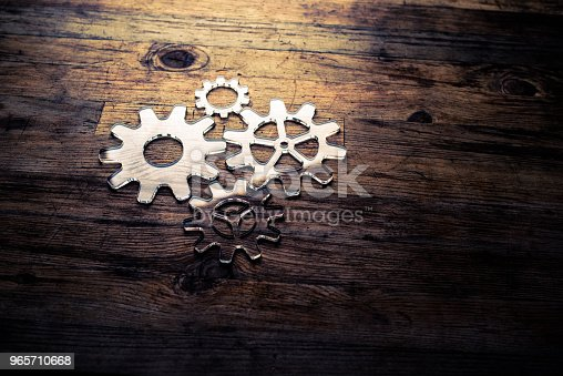 Four transparent gears on a wooden desk