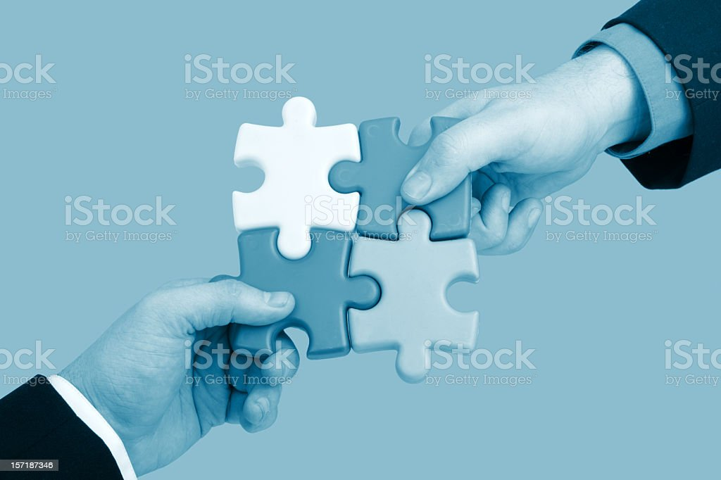 Partnership concept showing two men putting together puzzle royalty-free stock photo