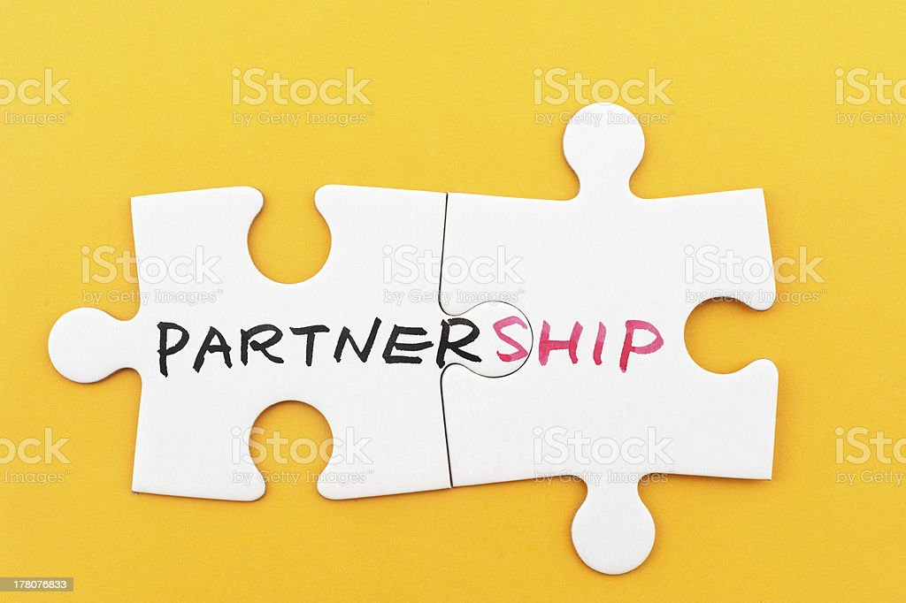 Partnership concept with two white puzzle pieces on yellow stock photo