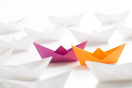 Two paper boats colored orange and pink among many white paper boats on white background.