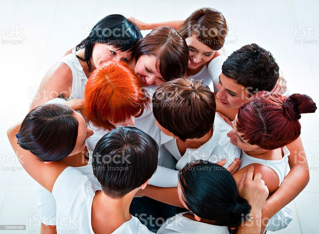 Partnership Group of happy women standing together in the circle, embracing and looking at each other. Elevated view. Adult Stock Photo