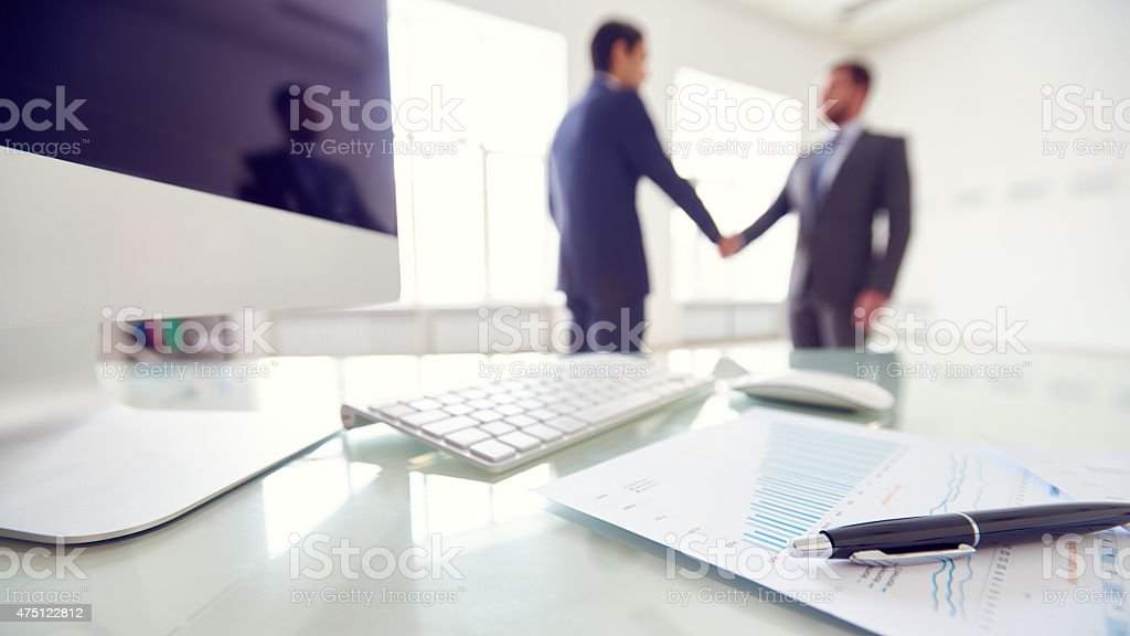 Partnership Ballpoint pen, document, computer on table in foreground; people shaking hands in background 2015 Stock Photo