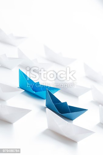 Two blue paper boats among many white paper boats on white background.