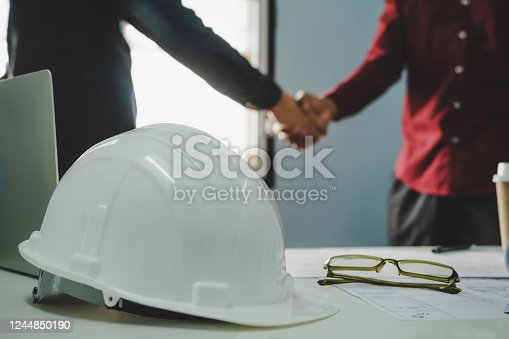 1055059750 istock photo Partnership. white safety helmet on workplace desk with construction worker team hands shaking after start up plan new project contract in office room at construction site, contractor meeting concept 1244850190