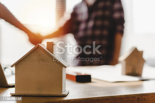 1055059750 istock photo Partnership. wooden house model on workplace desk with construction worker team hands shaking greeting start up plan new project contract in office center at construction site and contractor concept 1156085133