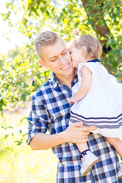 Partrait of father and daughter Daughter drassed like princess kissing her smiling dad in the cheek little girl kissing dad on cheek stock pictures, royalty-free photos & images