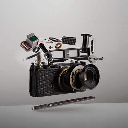 Parts and components of a disassembled analog vintage film camera floating in the air on white background