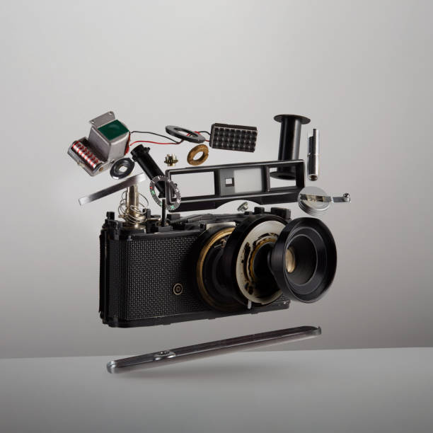 Parts and components of a disassembled analog vintage film camera floating in the air on white background stock photo