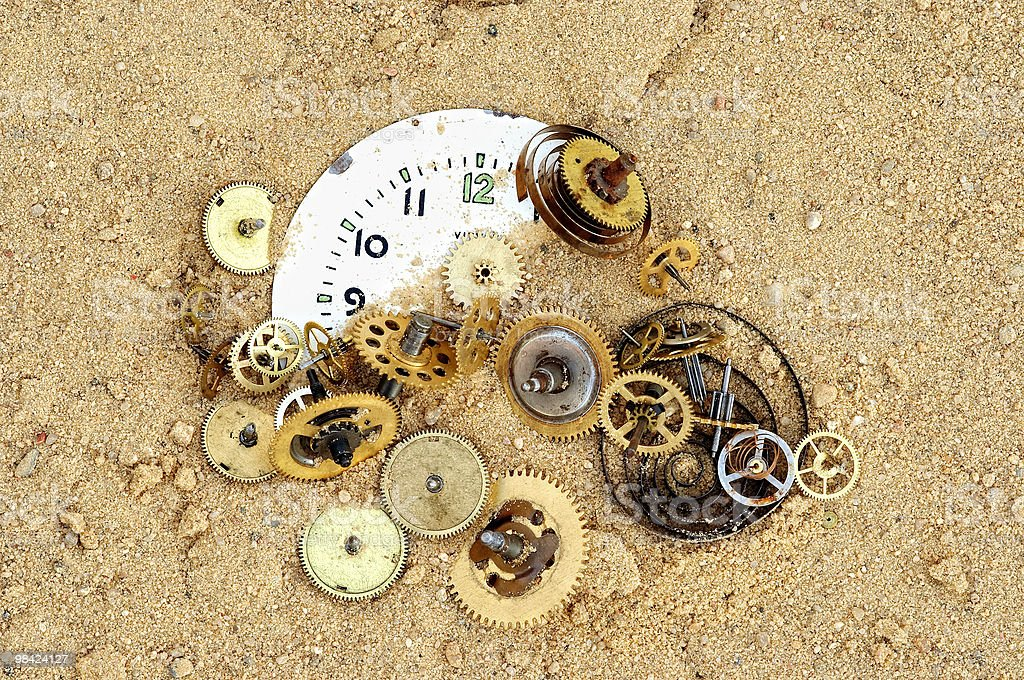 parts of clockwork mechanism on the sand royalty-free stock photo