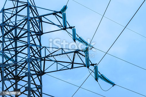 Parts of high voltage electricity tower or power tower or electricity pylon and line of electric wires against a blue cloudy sky. Steel lattice tower, to support an overhead power line.