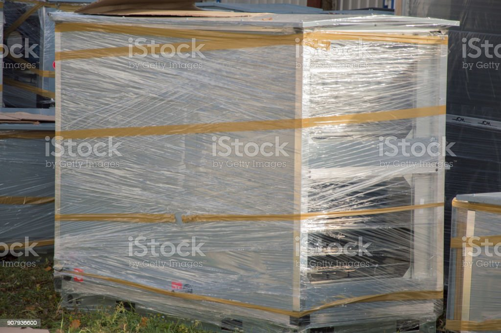Parts of the idustrial air handling units standing outdoor on the ground covered by grass stock photo
