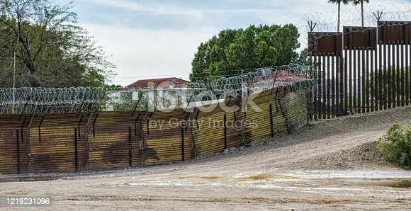 Parts of the Old and New Steel-Slat Border Wall Topped by Razor Wire (on the US Side) between Mexico and the United States with the Town of Los Algodones in the Background