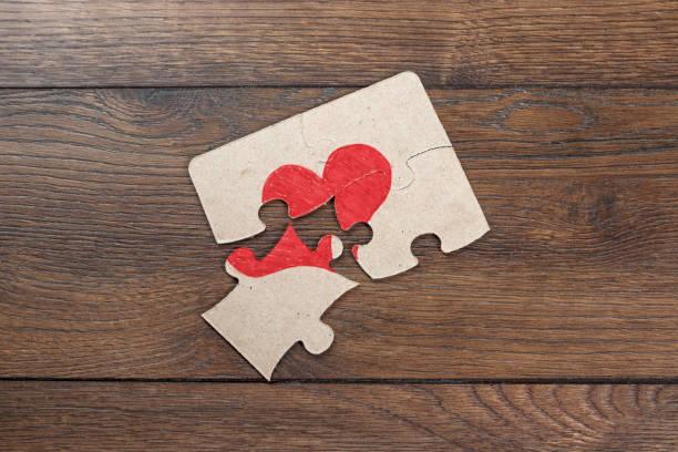 onderdelen van de puzzel vormen het hart, gebroken. het concept van de scheiding, ruzie, conflict. - liefdesverdriet stockfoto's en -beelden