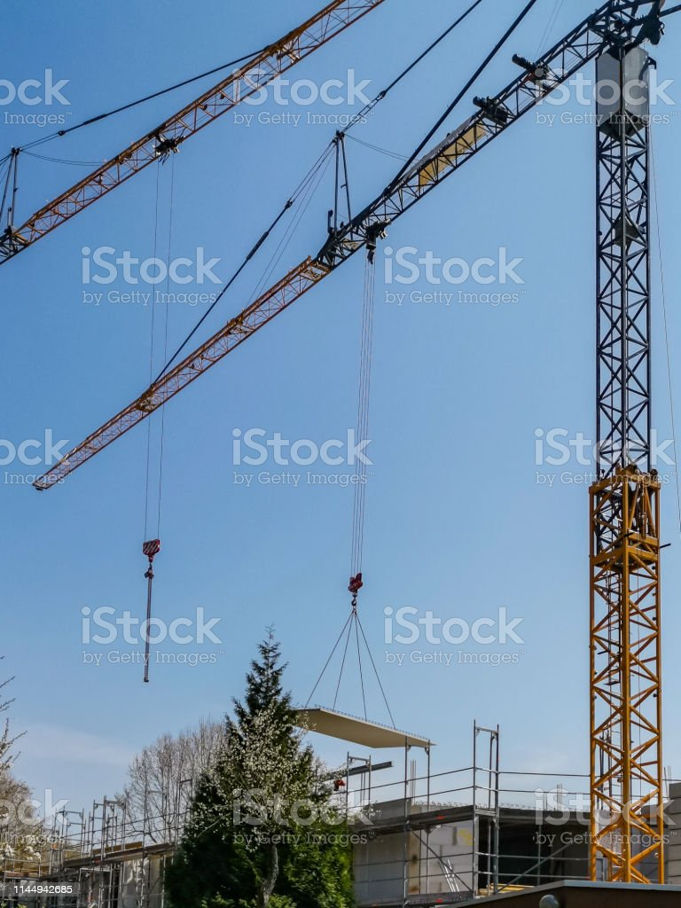 parts of two building cranes at work, one carrying a part of a...