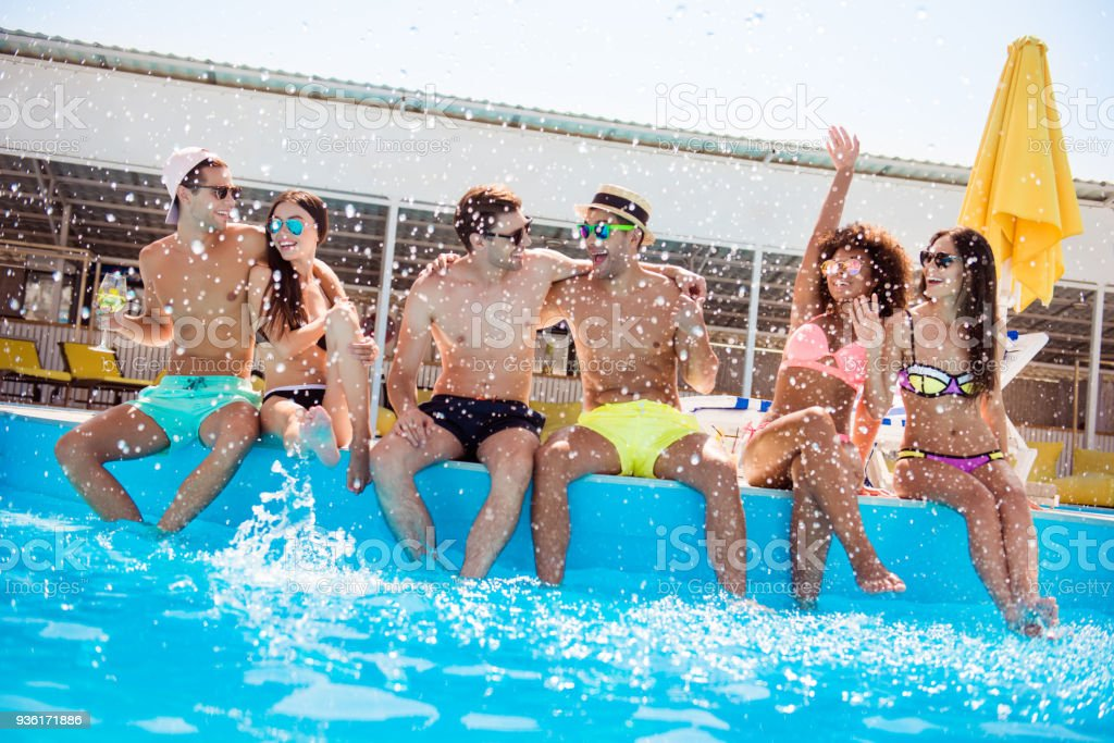 Party all day! Go crazy non stop. Six excited multi national tourists are enjoying at the pool sunny beach disco, with drinks, splashes of water all around, sitting by the pool, legs in clean water stock photo