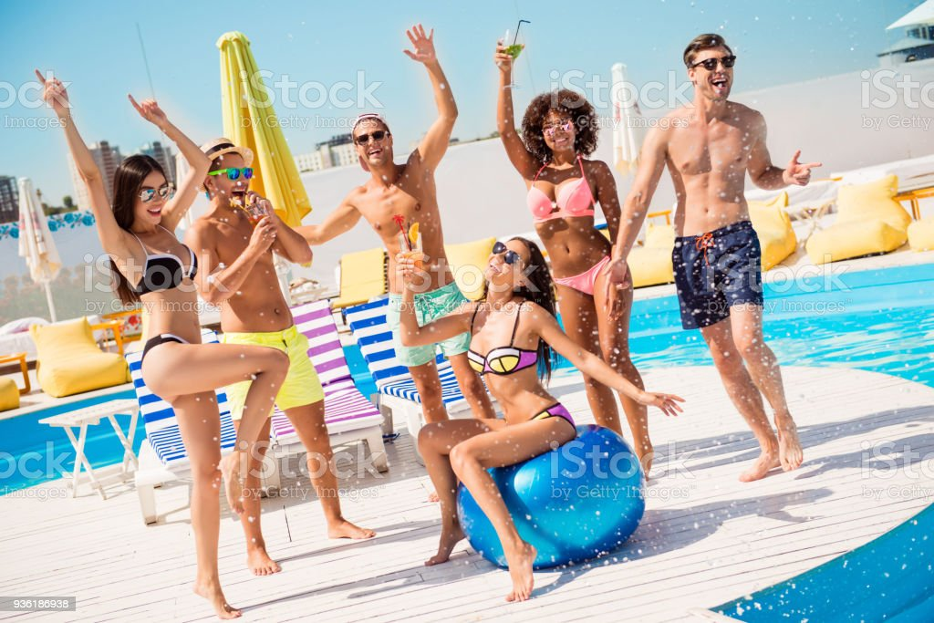 Party all day! Go crazy non stop. Six excited multi national tourists are enjoying at the pool sunny beach disco, with drinks, splashes of water all around! Brunette sit on big ribbon blue ballon stock photo