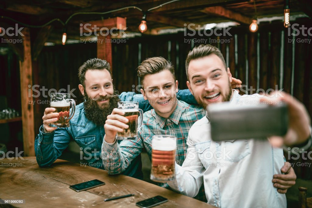 Party Animal Guys Taking Selfie And Drinking In Bar After Work stock photo