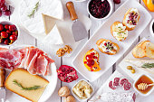 istock Party appetizers of assorted cheeses, meats and crostini, top view on white wood 1186418525