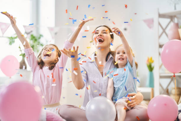 party at home Funny time. Mom and her children daughters are playing at home. Girls are throwing confetti. Family holiday and togetherness. carnival children stock pictures, royalty-free photos & images