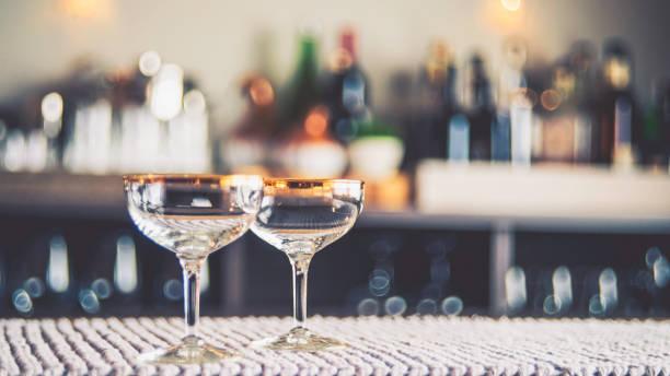 party hintergrund mit defokussierten flaschen und zwei leere gläser - goldene bar stock-fotos und bilder
