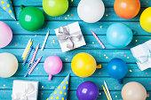パーティー誕生日表。カラフルな気球、ギフト、紙吹雪、カーニバルは、青いテーブル トップ ビューでキャップします。休日の供給。