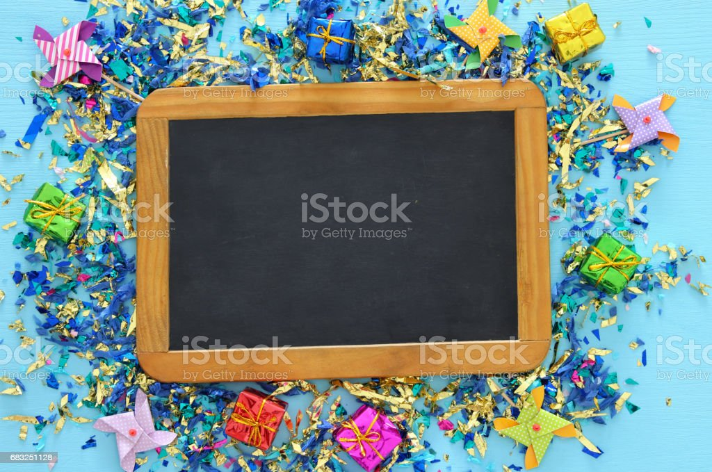 party blue background with colorful confetti and blackboard royalty-free stock photo