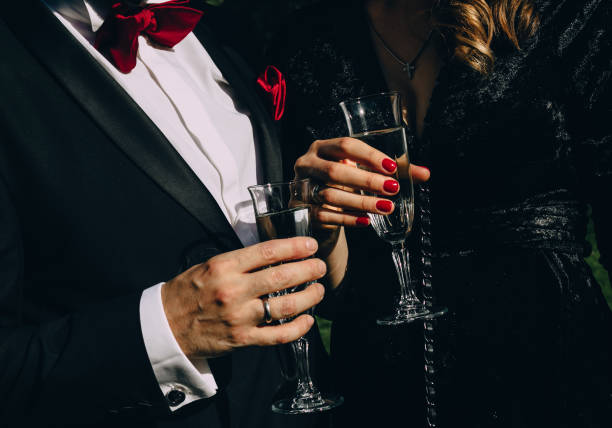 party champagne style black clothes red accessories party style man in black suit red butterfly woman in black clothes red manicure drink champagne tuxedo stock pictures, royalty-free photos & images