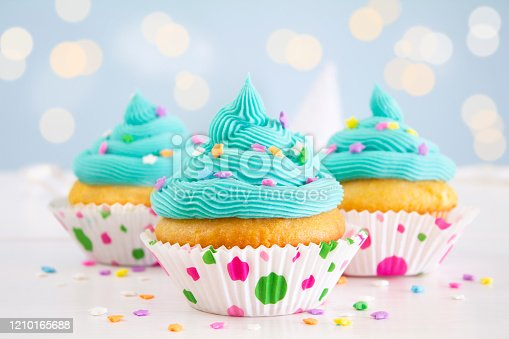 Vanilla and buttercream cupcakes with blue icing and sprinkles, on a blue background.