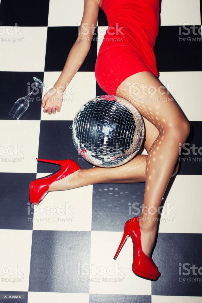 Party detail with woman legs and disco ball stock photo