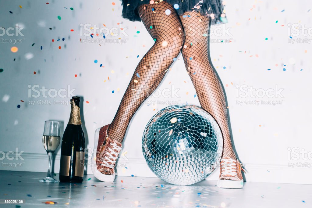 Party details of female legs and disco ball stock photo