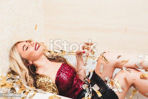Swanky fashion style party. Festive mood. Rich blonde girl enjoying her birthday with champagne in bathtub. Confetti around.