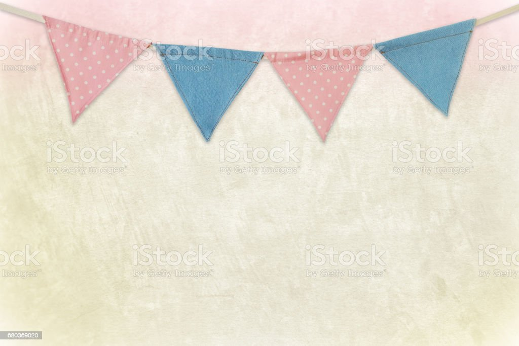 Party flags hanging on colored cement wall background, decorate items for festival, celebrate event royalty-free stock photo