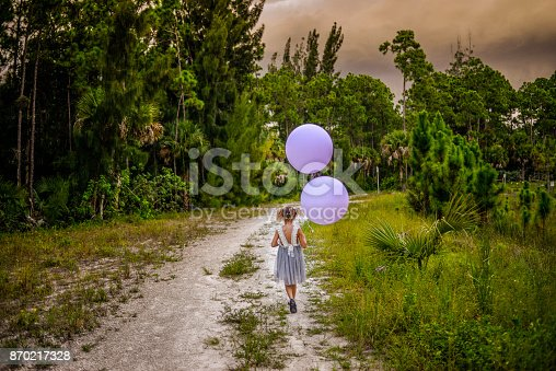 Adorable little girl in a pretty dress holds two big purple balloons in a nature setting at dusk