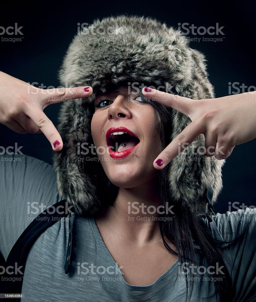 Party girl wearing fur hat showing victory sign royalty-free stock photo