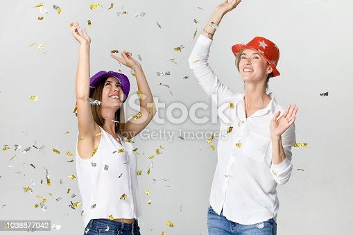 627933752istockphoto Party girlfriends with confetti and colorful hats. It is relaxation and dancing time 1038877042