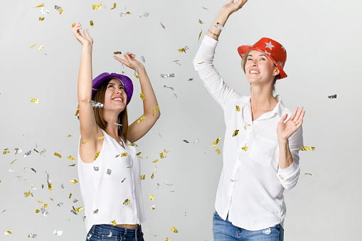 627933752 istock photo Party girlfriends with confetti and colorful hats. It is relaxation and dancing time 1038877042